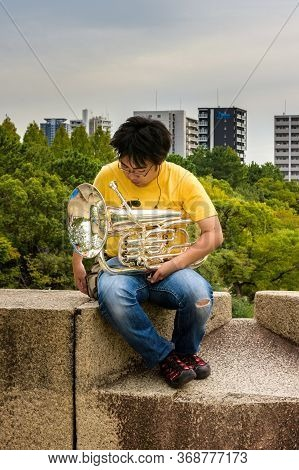 Osaka / Japan - October 1, 2017: Man Sitting On The Ramparts Of The Osaka Castle And Playing Trumpet