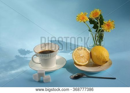 A White Cup Of Coffee On A Saucer, Next To A Lemon On A Saucer, A Teaspoon And Three Lumps Of Sugar.