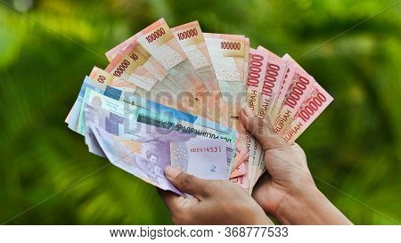 The Girl Is Holding Indonesian Money. Indonesian Rupee.