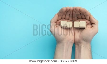 Wooden Cubes In Men's Hands Close Up. Business Concept For Growth Success Process. Copy Space