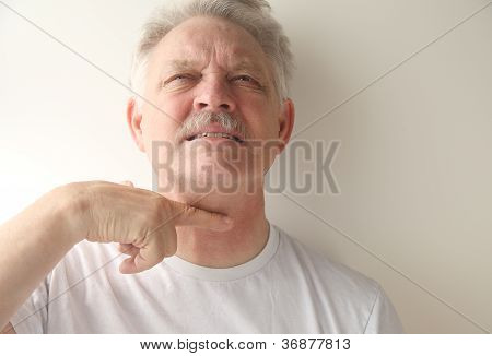 senior man gestures with finger across throat