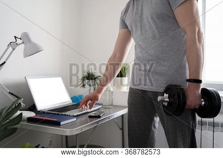 Workouts, Fitness At Home. Athletic Man Watching An Online Lesson On A Laptop, Working In A Home Off