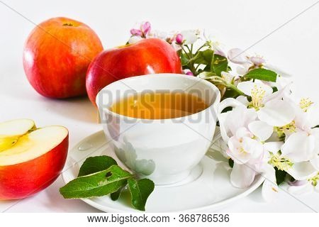 A Cup Of Fresh Apple Juice, A Ripe Red Apple, Apple Tree Flowers And A Sliced apple In Two On A Wh