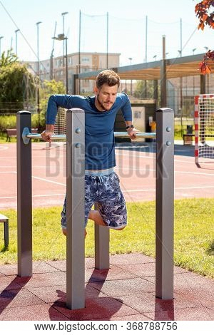 Young Handsome Man Training At Parallel Bars In The Playground On A Sunny Day