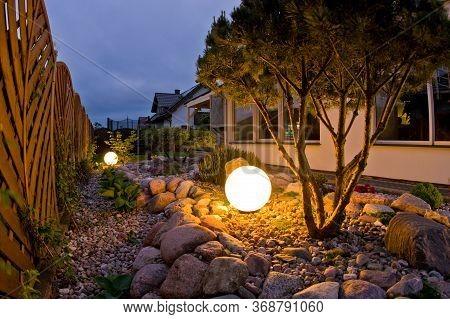 Home Garden At Night, Illuminated By Globe Shaped Lights.