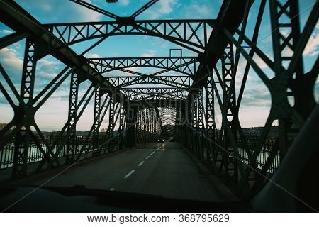 Tunel Of A Dark Metal Bridge For Cars Over A River.