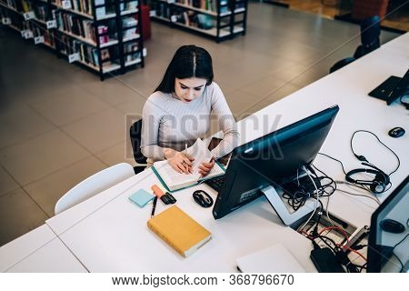 Insightful Female Student Reading Textbook And Using Computer While Studying In Library