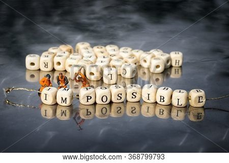 Miniature Model Of People Remove Wooden Cubes With Word Impossible To Possible. Personal Development
