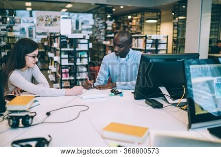 Focused Fellows Studying In Library In Documents While Sitting At Table