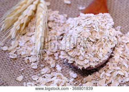 Rolled Oats Or Oat Flakes On Wooden Spoon