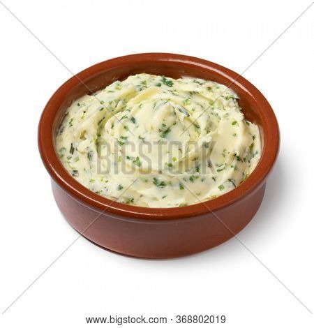 Bowl with fresh made herb butter close up isolated on white background