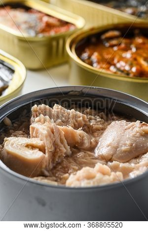 Tuna Tin Can Close Up Over Cans With Different Preserve Of Fish And Conserve Seafood, Opened And Clo