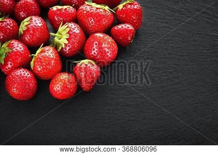 Bunch Of Strawberries Background. Strawberries On A Dark Slate Stone. Background Image With Copy Spa