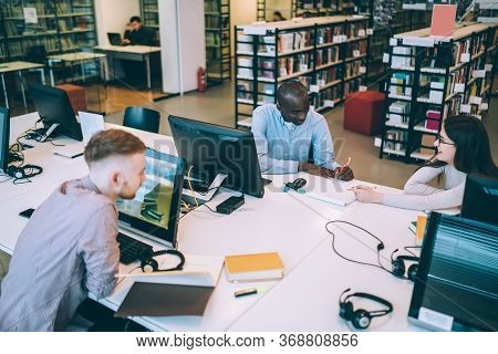 Joyful Fellows Making Homework In Library In Documents While Sitting At Table