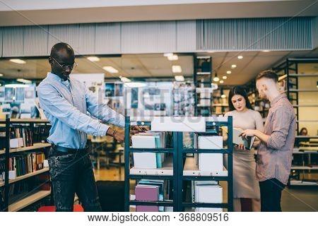 Black Student Choosing Books Near Classmates In Modern University