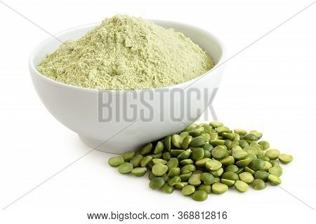 Dried Green Pea Flour In A White Ceramic Bowl Next To A Pile Of Green Split Peas Isolated On White.