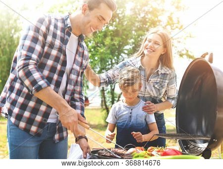 Happy Family Having Barbecue With Modern Grill Outdoors On Sunny Day