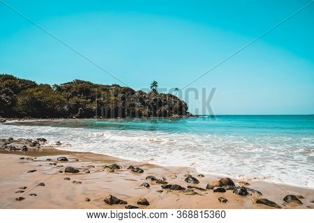 Beautiful Secluded Beach On An Isolated Island. Blue Water And White Waves Spume On A Sandy Beach Wi