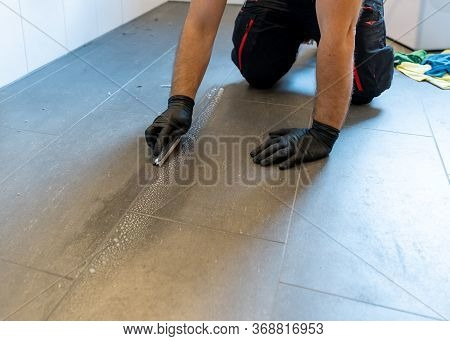A Professional Cleaner Cleaning Grout With A Brush Blade And Foamy Soap On A Gray Tiled Bathroom Flo