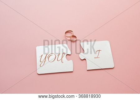 Two White Disconnected Puzzles With The Inscription You And I And Two Gold Wedding Rings On A Pink B