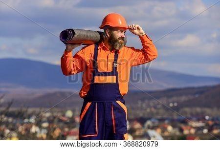 Roof Installation. Man Hard Hat Work Outdoor Landscape Background. Building House. Apply Plastic Coa