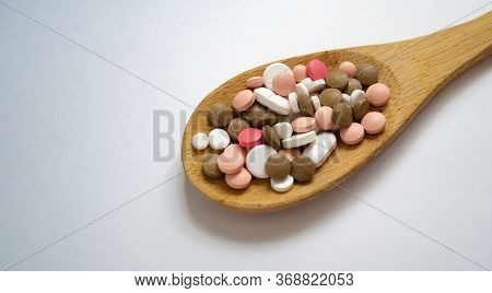Mixed Medicine Pills, Tablets On Wooden Spoon On White Background With Space For Text. Different Pil