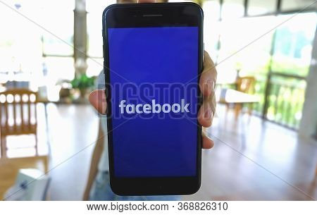 Chiang Mai, Thailand - May 23, 2020 : Woman Holds Smart Phone With Facebook Application On The Scree