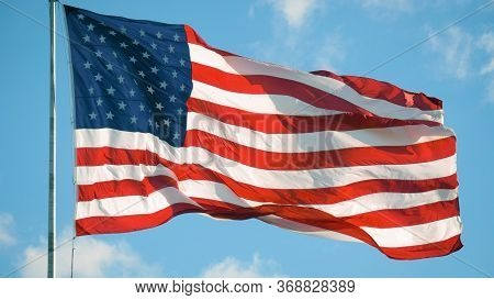 American Flag Blowing In The Wind With A Blue Sky Background. Usa American Flag. Memorial Day, Indep