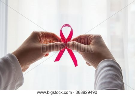 Hands Holding Pink Ribbon With White Background. Breast Cancer Awareness Month. Breast Cancer Concep