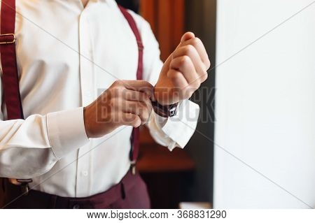 A Groom Putting On Cuff-links As He Gets Dressed In Formal Wear. A Man Straightens Cufflinks. Grooms