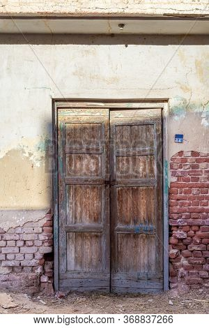 Closed Wooden Weathered Door And Shabby Old Grunge Red Bricks Wall In Abandoned District