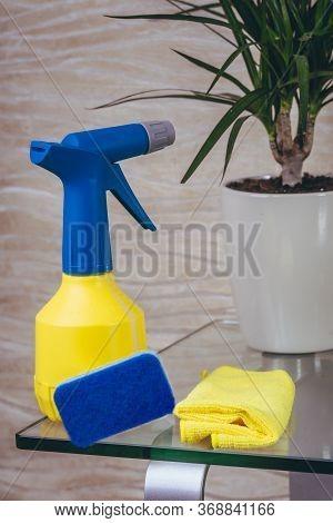 A Detergent In A Yellow Blue Cap Bottle, A Rag, Bast Lies On A Glass Table. Flowerpot. Quarantined A