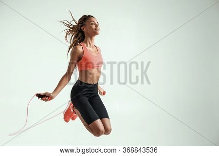 Flying. Happy And Young African Woman With Perfect Body Skipping Rope While Exercising In Studio Aga