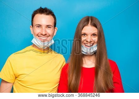 Happy Love Couple Remove Protective Mask Isolated On Blue Background. End Of Coronavirus Pandemic, Q
