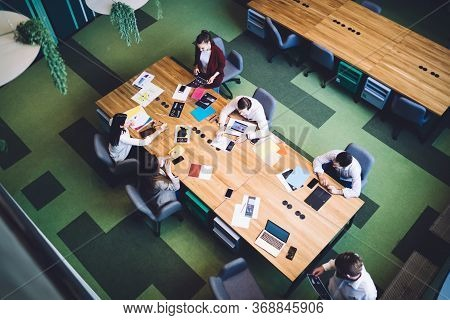 Women And Men Managers Sitting At Meeting Table In Corporation