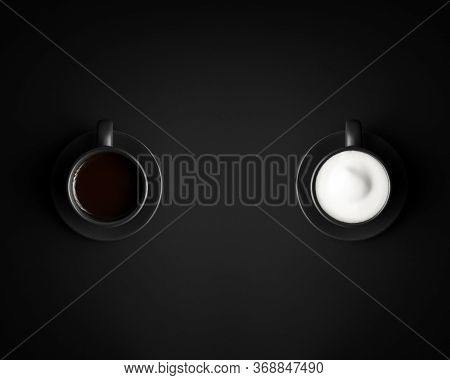 Cappuccino Versus Black Coffee. Two Black Cups And Saucers On Black Background. One With Cappuccino,