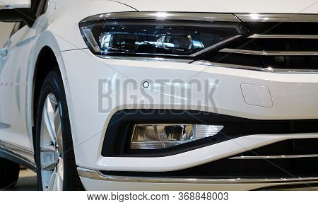 Modern Luxury White Car, Front View. Close-up Headlight, Part Of The Front Bumper, Radiator Grill, F