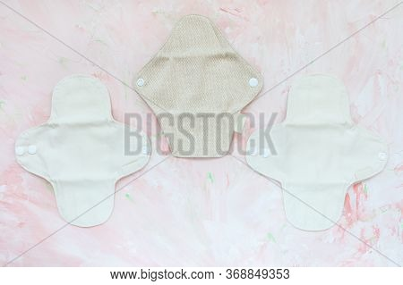 Three White And Beige Washable Healthy Reusable Menstrual Pads, Sanitary Cotton On Pink Background,