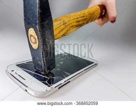 A Hammer That Hits A Smartphone Resting On A White Surface, Shattering The Display.