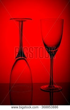 Two Empty Wine Glasses Isolated On Red Background.