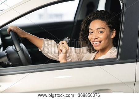 New Auto. African American Woman Showing Car Key Sitting In Drivers Seat In New Vehicle In Dealershi