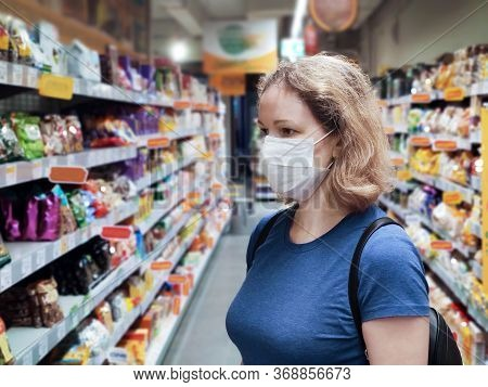 Coronavirus And Retail Concept, Young Woman Wearing Medical Mask Looks At Grocery In Supermarket. Co