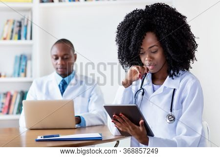 African American Medical Student At Digital Tablet Computer With Male Scientist At Hospital