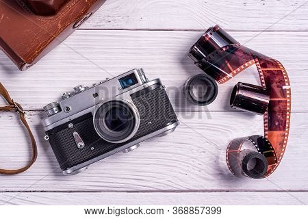 Vintage Film Rangefinder Camera With Leather Case And Photographic Film On White Wooden Table. The V