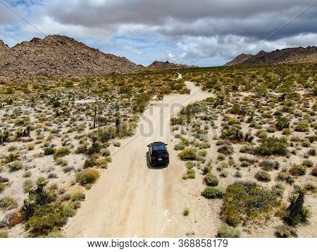 Aerial View Of 4x4 Car Driving Off Road In The Desert. Joshua Tree National Park. American National