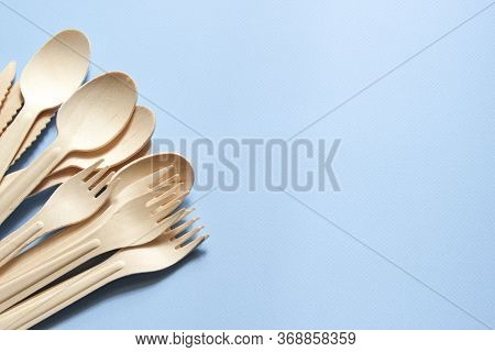 Eco-friendly Tableware. Spoons, Forks, Knives Made Of Wood. Tableware Is On The Left Side