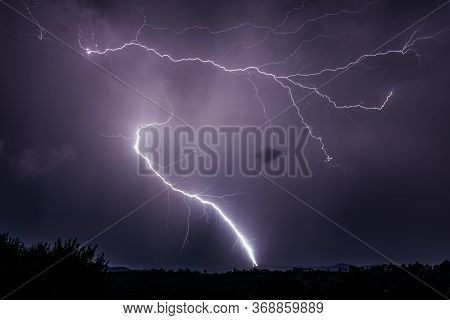 Two Dramatic Lightnings Discharging Over The Ground And Purple Sky On At Night In Romania Over Rural