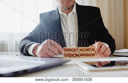 Goal Achievement Concept. Man Stacks Wooden Blocks With The Words Mission, Vision, Target And Achiev