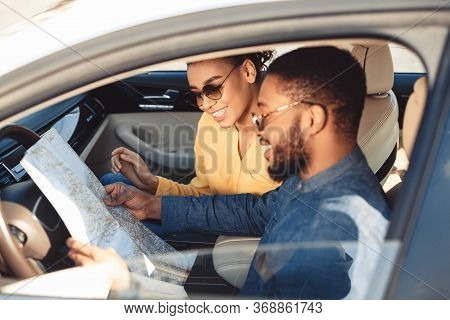 Car Trip. Happy Black Spouses Looking At Road Map Sitting In Car Traveling On Summer Vacation. Selec