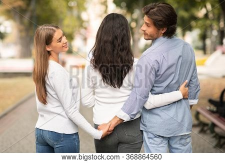 Infidelity. Cheating Boyfriend Holding Hands With Girlfriends Best Friend Walking Together In Park O